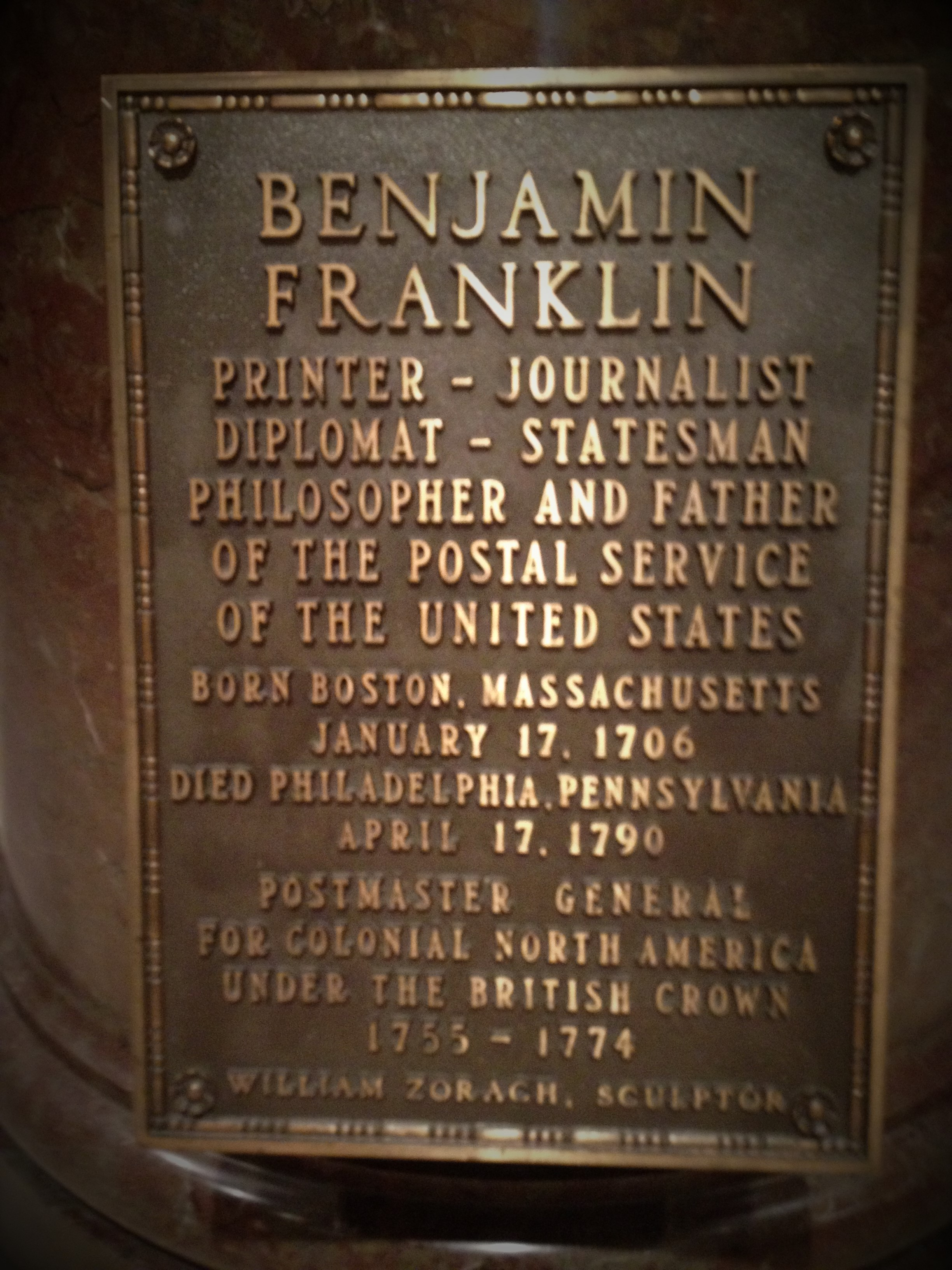The inscription of the statue of Benjamin Franklin at the National Postal Museum in Washington, D.C. identifies him as a printer, a journlist, a diplomat, a statesman, a philosopher, and the father of the United States Postal Service. Prior to the American Revolution, Franklin served as Postmaster General for Colonial North America under the British. Photo credit: L. Tripoli